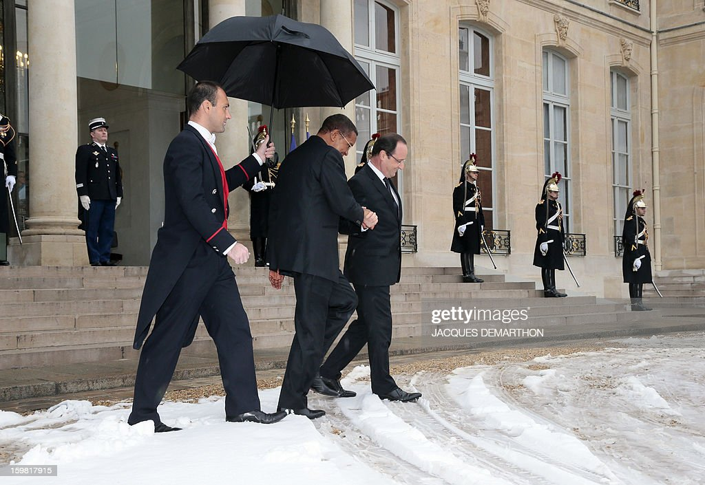 French President Francois Hollande (R) and Tanzanian President Jakaya Kikwete (C) walk in the snow covered courtyard of the presidential Elysee Palace after a meeting on January 21, 2013 in Paris.