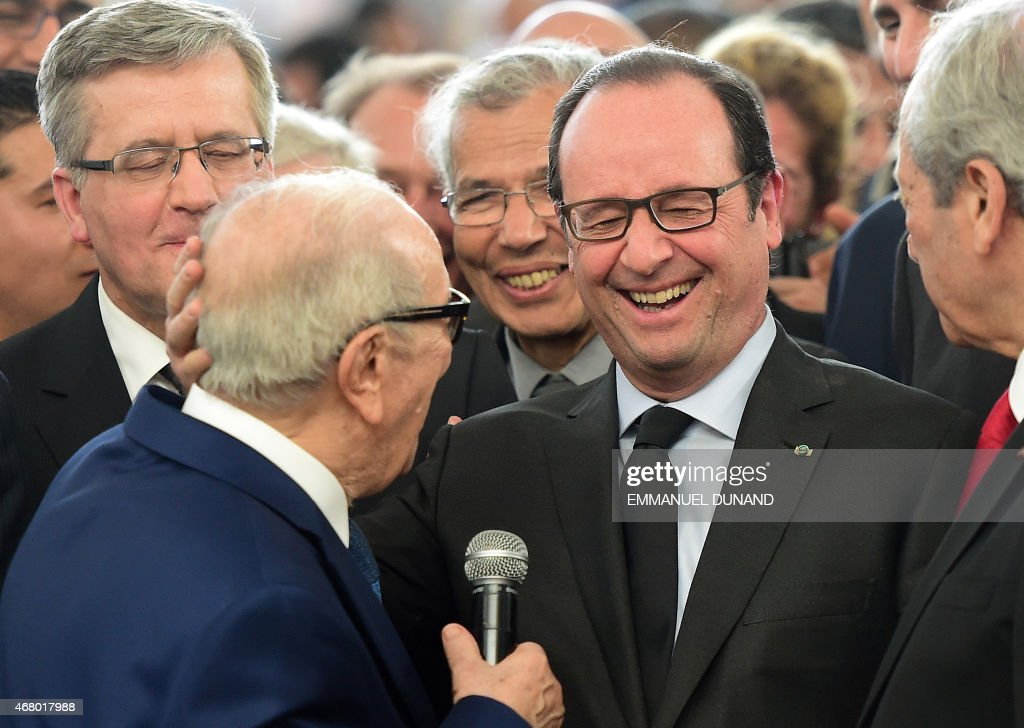 French President Francois Hollande (R) and Tunisian President Beji Caid Essebsi share a light moment after Essebi called the French President 'Francois Mitterand', during a speech following a musical hommage in Tunis, on March 29, 2015 in honour of the victims of the massacre of foreign tourists at the country's national museum.