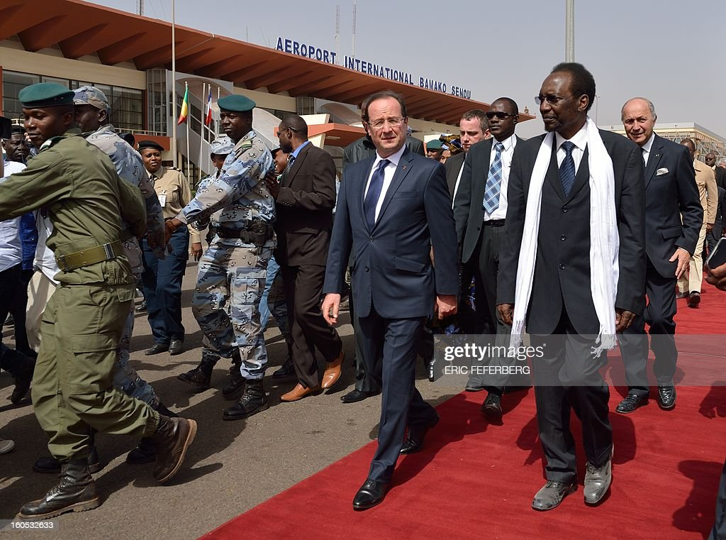 French President Francois Hollande (C) arrives with Mali's interim president Dioncounda Traore (R) at the Bamako airport on February 2, 2013. President Francois Hollande received a rapturous welcome today as he visited Mali to push for African troops to take over a French-led offensive that drove back Islamist rebels from the country's desert north. POOL