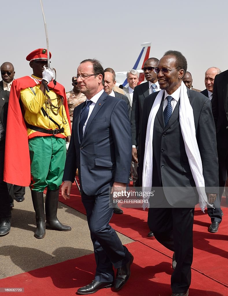 French President Francois Hollande (L) arrives with Mali's interim president Dioncounda Traore (R) at the Bamako airport on February 2, 2013. Hollande received a rapturous welcome today as he visited Mali to push for African troops to take over a French-led offensive that drove back Islamist rebels from the country's desert north. POOL