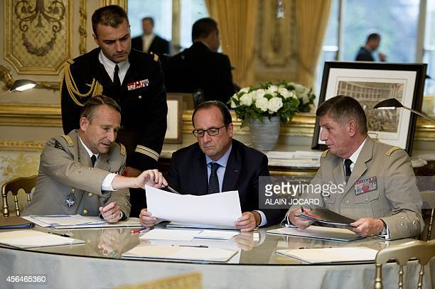 French president Francois Hollande attends a meeting focused on the Iraqi conflict with French Army Chief of Staff General Pierre de Villiers and...