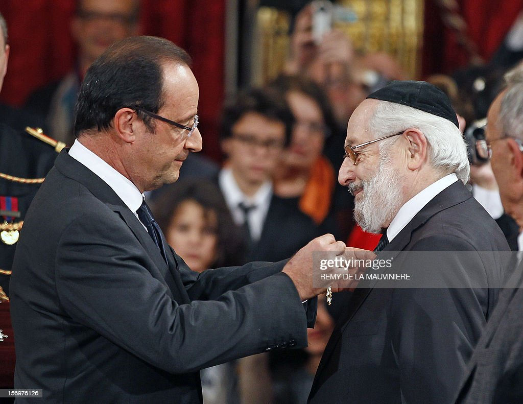French President Francois Hollande (L) awards Alain Goldman, the grand rabbi of Paris, with the Grand Officier of the Legion of Honor medal during an award ceremony on November 26, 2012 at the Elysee Palace in Paris. AFP PHOTO POOL REMY DE LA MAUVINIERE