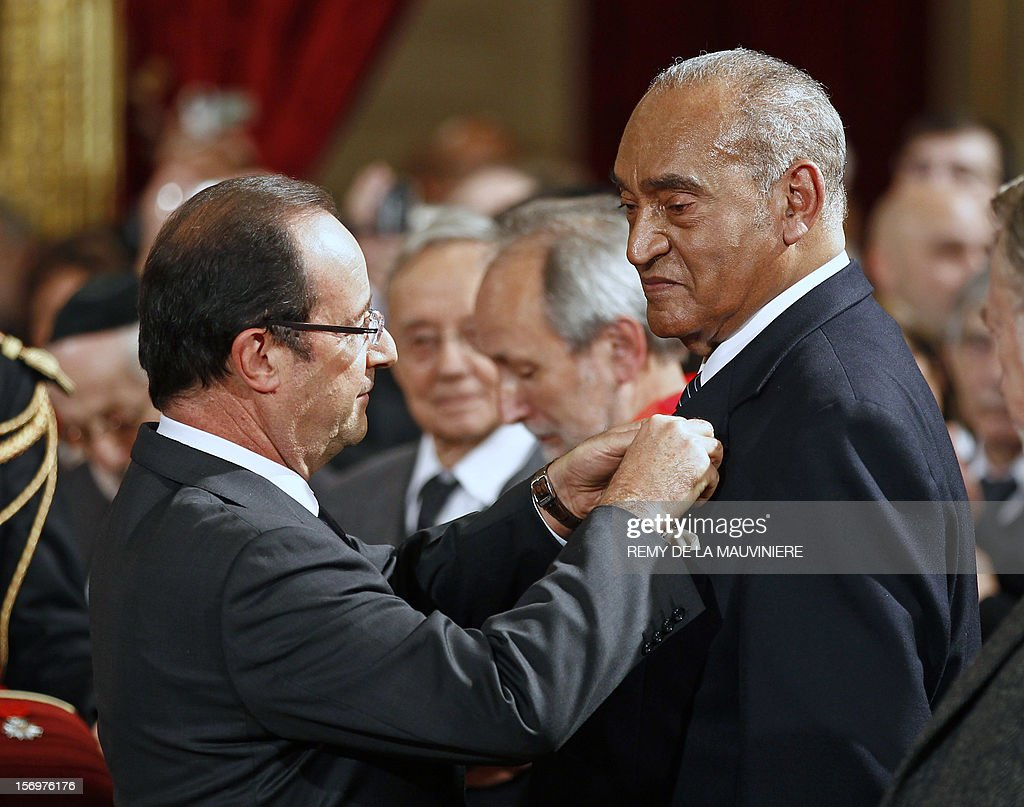French President Francois Hollande (L) awards former Mayotte deputy Henry Jean Baptiste with the Officer of the Legion of Honor medal during an award ceremony on November 26, 2012 at the Elysee Palace in Paris. AFP PHOTO POOL REMY DE LA MAUVINIERE