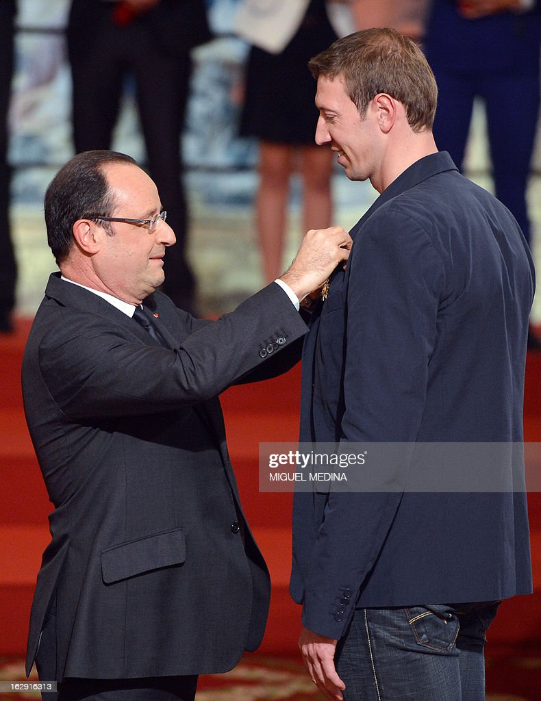 French President Francois Hollande (L) awards French swimmer Alain Bernard, gold medalist at the 2012 London olympics games, with the French Legion d'Honneur during a ceremony on March 1, 2013 in Paris.