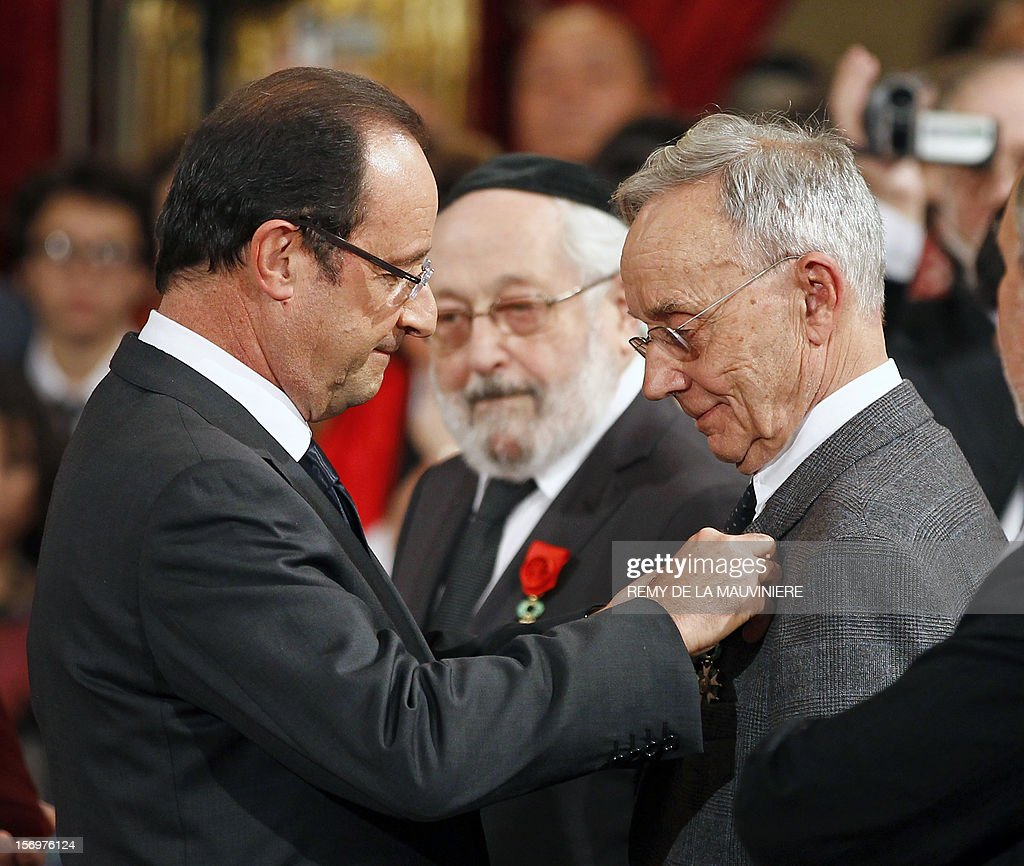 French President Francois Hollande (L) awards member of Science Academy Pierre Joliot with the Grand Officier of the Legion of Honor medal during an award ceremony on November 26, 2012 at the Elysee Palace in Paris.