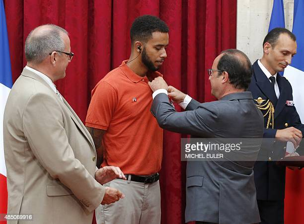 French President Francois Hollande awards offduty US serviceman Anthony Sadler and British business consultant Chris Norman with France's top Legion...