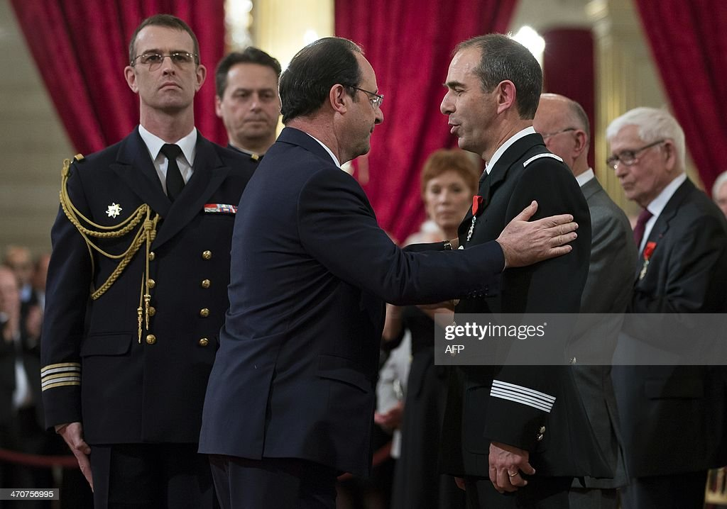 French President Francois Hollande (L) awards the deputy director of the firefighters' federation Denis Musson with the Chevalier of the Legion of Honor medal during a ceremony at the Elysee Palace in Paris, on February 20, 2014.