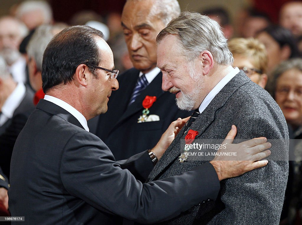 French President Francois Hollande (L) Bernard Faivre d'Arcier after awarding him with the Officer of the Legion of Honor medal during an award ceremony on November 26, 2012 at the Elysee Palace in Paris.