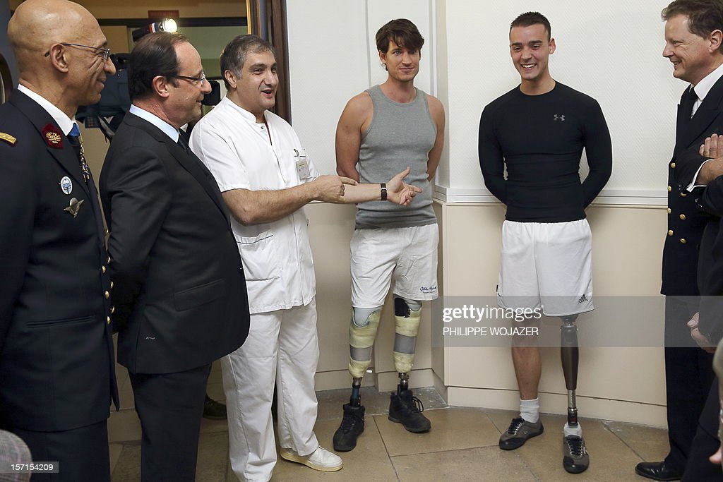 French President Francois Hollande (2ndL) chat with soldier with prosthetic limbs while visiting the military hospital of the Hotel des Invalides in Paris on November 29, 2012. POOL