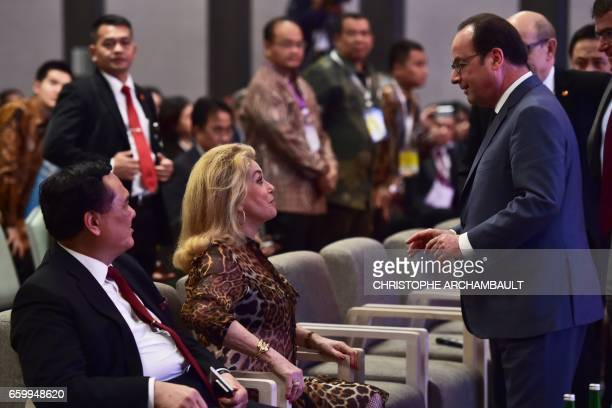 French President Francois Hollande chats with French actress Catherine Deneuve in Jakarta on March 29 2017 Hollande is on the last day of his Asian...