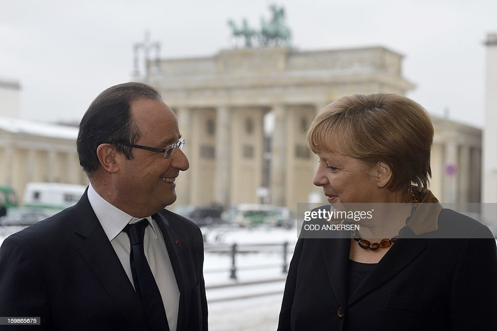 French President Francois Hollande (L) chats with German Chancellor Angela Merkel as they pose in front of the Brandenburg Gate as they arrive at the French Embassy in Berlin on January 22, 2013 for a meeting as part of the celebration to mark 50 years since the Elysee Treaty launched after WWII the French-German cooperation. In signing the landmark treaty on January 22, 1963, then French president Charles de Gaulle and West German chancellor Konrad Adenauer sealed a new era of reconciliation between the former foes which has since driven European unity. AFP PHOTO / ODD ANDERSEN