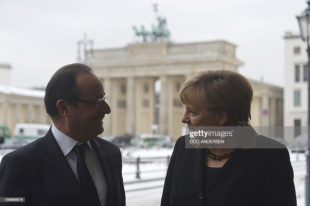 French President Francois Hollande (L) chats with German Chancellor Angela Merkel as they pose in front of the Brandenburg Gate as they arrive at the French Embassy in Berlin on January 22, 2013 for a meeting as part of the celebration to mark 50 years since the Elysee Treaty launched after WWII the French-German cooperation. In signing the landmark treaty on January 22, 1963, then French president Charles de Gaulle and West German chancellor Konrad Adenauer sealed a new era of reconciliation between the former foes which has since driven European unity.
