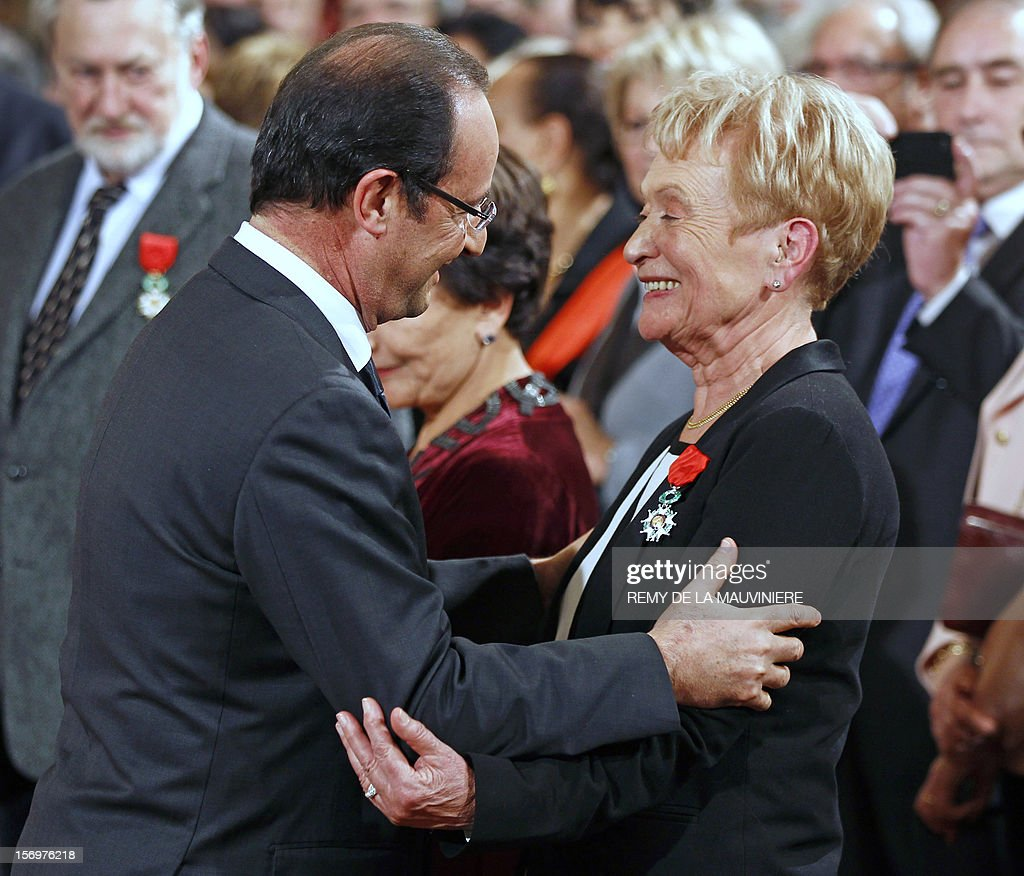 French President Francois Hollande (L) congratulates French general counsellor Marie Therese Delrieu, after awarding her with the Chevalier of the Legion of Honor medal during an award ceremony on November 26, 2012 at the Elysee Palace in Paris. AFP PHOTO POOL REMY DE LA MAUVINIERE