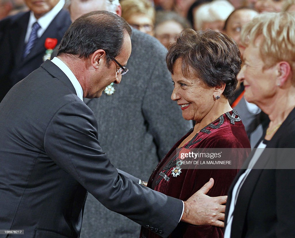 French President Francois Hollande (L) congratulates Tunisian journalist Souhayr Belhassen, after awarding her with the Chevalier of the Legion of Honor medal during an award ceremony on November 26, 2012 at the Elysee Palace in Paris. AFP PHOTO POOL REMY DE LA MAUVINIERE