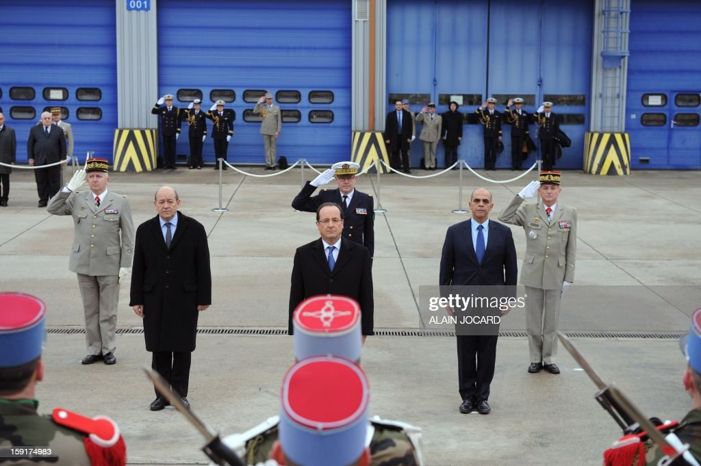 French president Francois Hollande (C), Defence minister Jean-Yves Le Drian (L) and War veterans minister Kader Arif (R) review troops on January 9, 2013 in Olivet, near Orleans, central France, as part of a visit to present his New Year's wishes to the French armed forces.