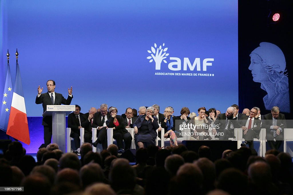 French President Francois Hollande (L) delivers a speech as ministers and other officials listen during the opening ceremony of the 95th French Mayors congress, on November 20, 2012 in Paris.