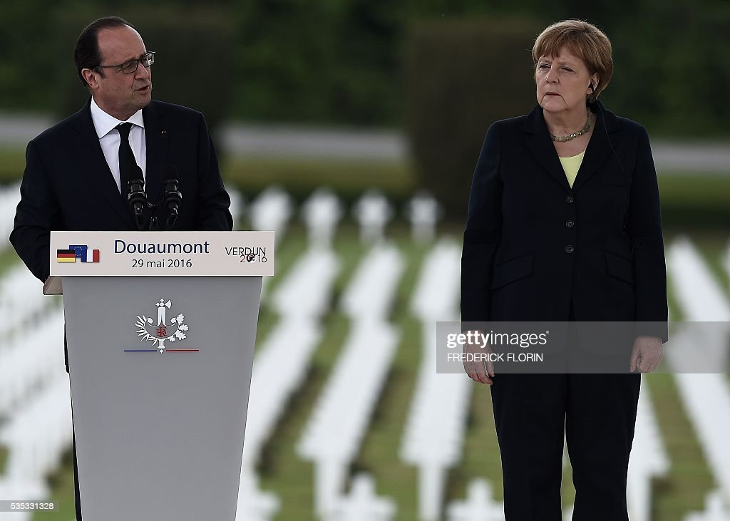 French President Francois Hollande (L) delivers a speech next to German Chancellor Angela Merkel during a remembrance ceremony to mark the centenary of the battle of Verdun, at the Douaumont Ossuary (Ossuaire de Douaumont), northeastern France, on May 29, 2016. The battle of Verdun, in 1916, was one of the bloodiest episodes of World War I. The offensive which lasted 300 days claimed more than 300,000 lives. / AFP / FREDERICK