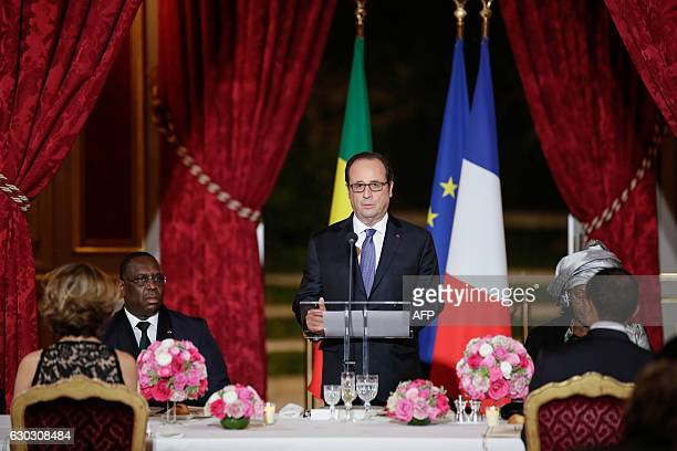 French President Francois Hollande delivers a speech next to his Senegalese counterpart Macky Sall during a state dinner at the Elysee Palace in...