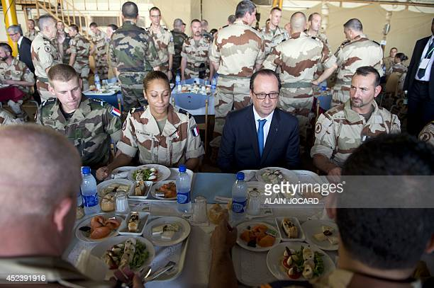 French president Francois Hollande eats with French soldiers at the Kossei airforce base as part of a work visit to Chad on July 19 2014 in N'Djamena...