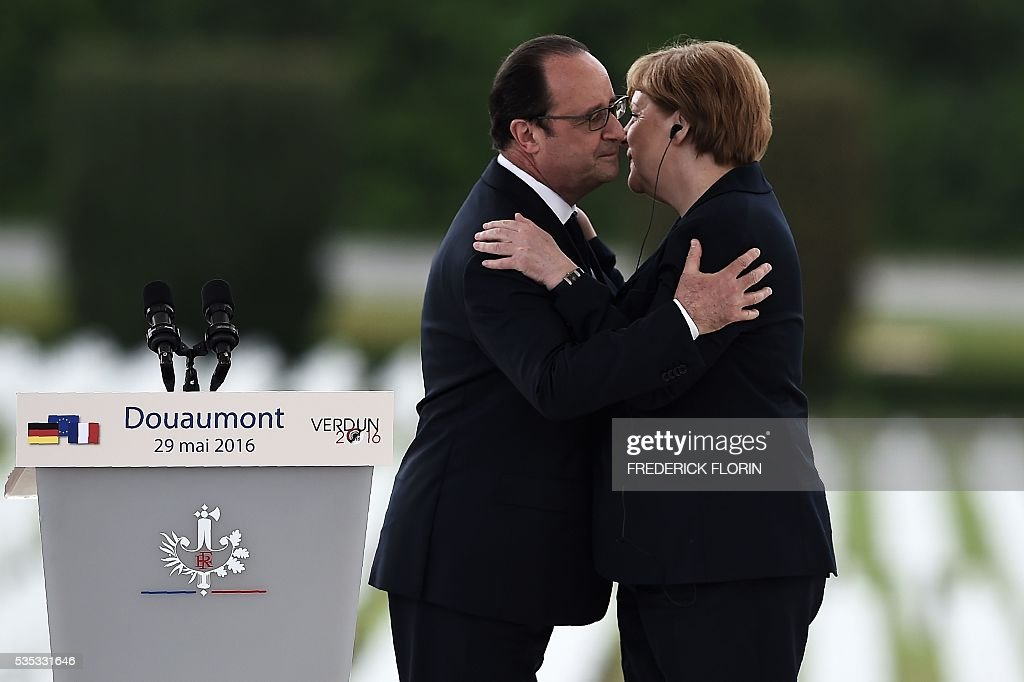 French President Francois Hollande (L) embraces German Chancellor Angela Merkel during a remembrance ceremony to mark the centenary of the battle of Verdun, at the Douaumont Ossuary (Ossuaire de Douaumont), northeastern France, on May 29, 2016. The battle of Verdun, in 1916, was one of the bloodiest episodes of World War I. The offensive which lasted 300 days claimed more than 300,000 lives. / AFP / FREDERICK