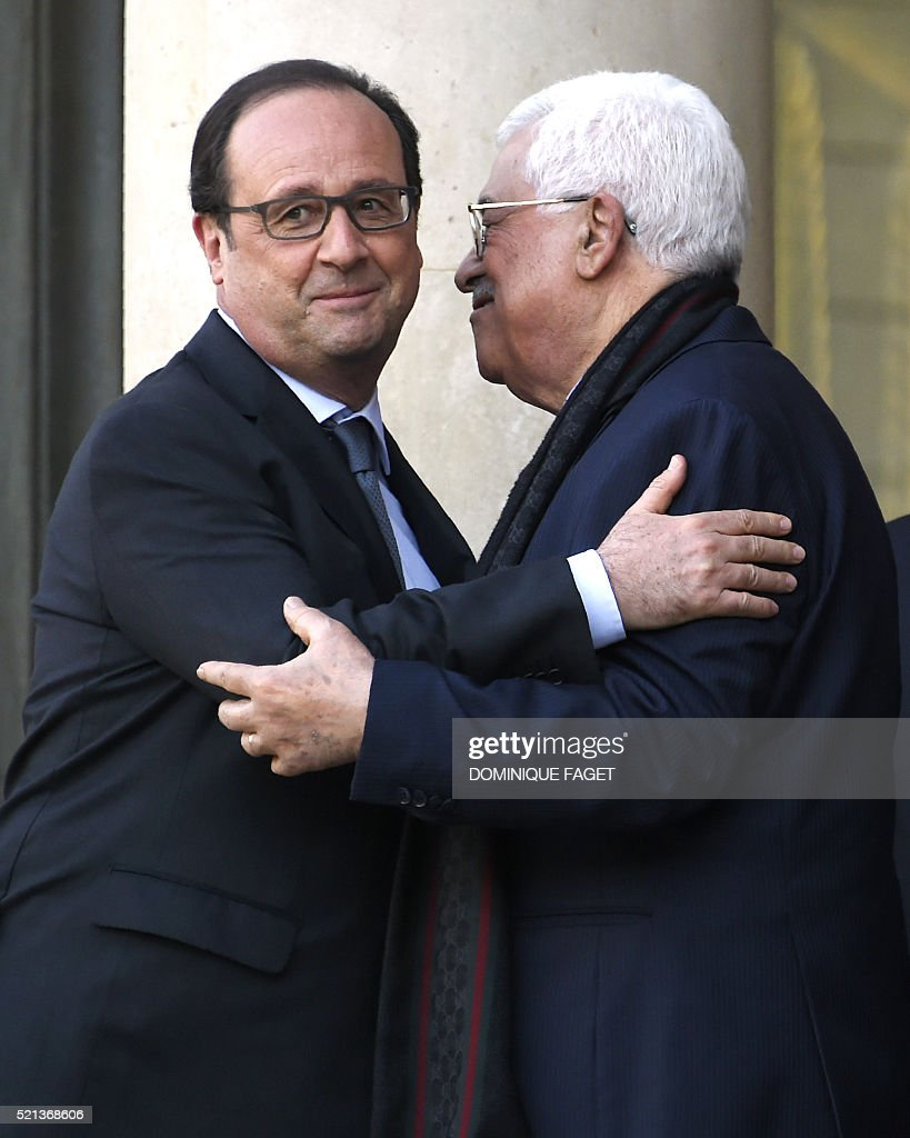 French President Francois Hollande embraces Palestinian president Mahmud Abbas after their meeting at the Elysee Palace in Paris on April 16 2016...