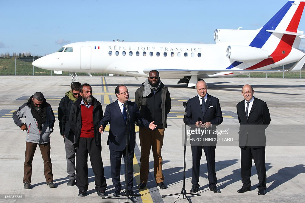 French president Francois Hollande (4thL) flanked by (LtoR) former French hostages Marc Feret, Pierre Legrand, Daniel Larribe and Thierry Dol and French Foreign minister Laurent Fabius and Defence Minister Jean-Yves Le Drian, delivers a speech upon the hostages' arrival at the military airport of Villacoublay outside Paris, on October 30, 2013. Four French hostages who were kidnapped by Al-Qaeda in the Islamic Maghreb in northern Niger in 2010 have been released on October 29. Frenchmen , Daniel Larribe,and were working for French nuclear giant Areva when they were kidnapped on September 16, 2010, from a uranium compound in Arlit, north-central Niger.
