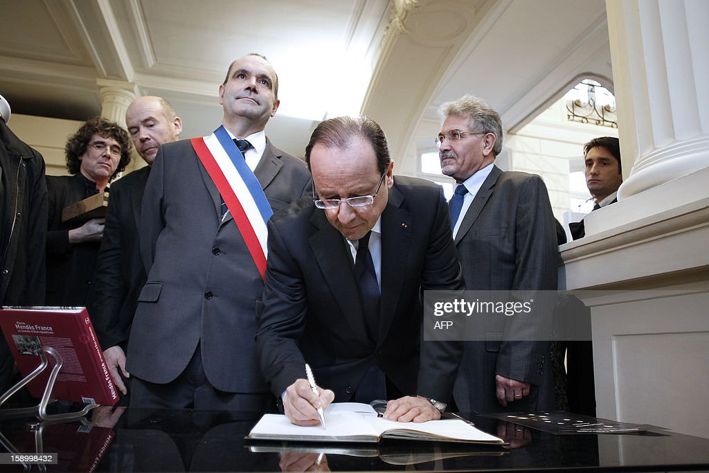 French President Francois Hollande (C) flanked by Franck Martin (CL), Louviers' Mayor, signs the guest book after visiting on January 5, 2013 in Louviers, northwestern France, the exhibition 'Pierre Mendes-France', dedicated to Pierre Mendes-France, late socialist Prime Minister (1954-55) and former Louviers' Mayor, during a visit in Normandy.
