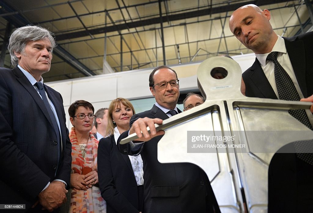 French President Francois Hollande (C) flanked by French Agriculture minister and Government spokesperson Stephane Le Foll (L) and Mecachrome's French Chief Executive Officer Arnaud de Ponnat, visits the MK Automotive Mecachrome plant on May 4, 2016 in Sable-sur-Sarthe, northwestern France. / AFP / JEAN