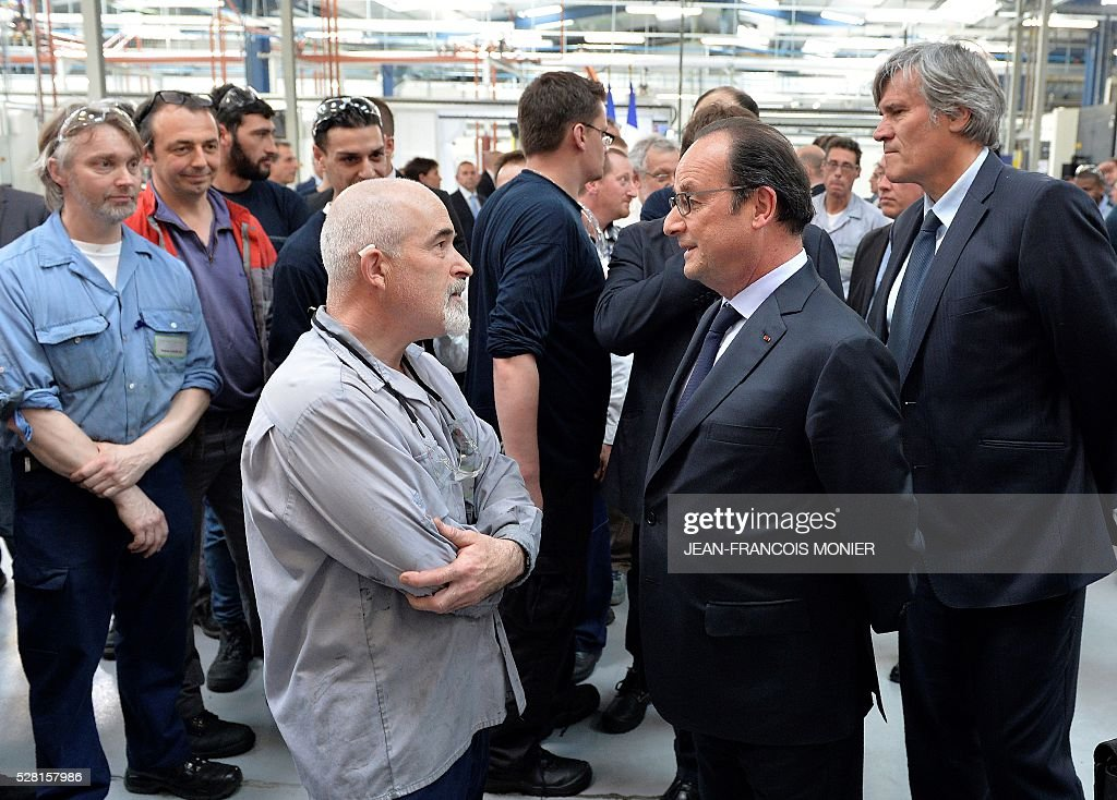 French President Francois Hollande (C) flanked by French Agriculture minister and Government spokesperson Stephane Le Foll (R), talks with a worker during a visit at the MK Automotive Mecachrome plant on May 4, 2016 in Sable-sur-Sarthe, northwestern France. / AFP / JEAN