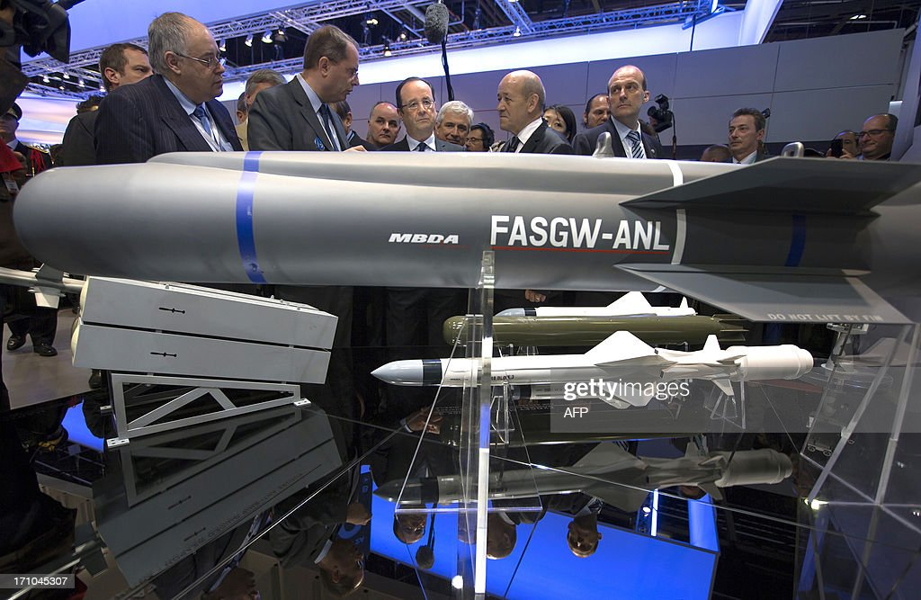 French President Francois Hollande (CL) flanked by French Defence Minister Jean-Yves Le Drian (CR) looks at missiles manufactured by French weaponry firm MBDA during his visit of the 50th International Paris Air show, at Le Bourget airport, near Paris on June 21, 2013.