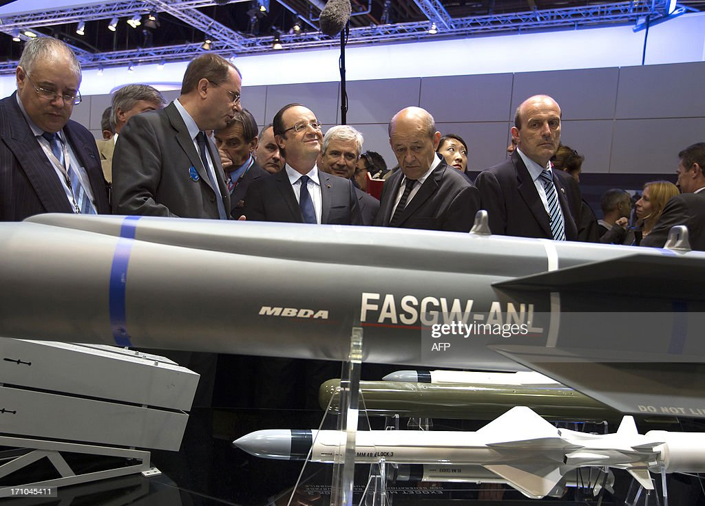 French President Francois Hollande (CL) flanked by French Defence Minister Jean-Yves Le Drian (CR) and MBDA Missile Systems company CEO Antoine Bouvier (2ndL) looks at missiles manufactured by MBDA during his visit of the 50th International Paris Air show, at Le Bourget airport, near Paris on June 21, 2013.