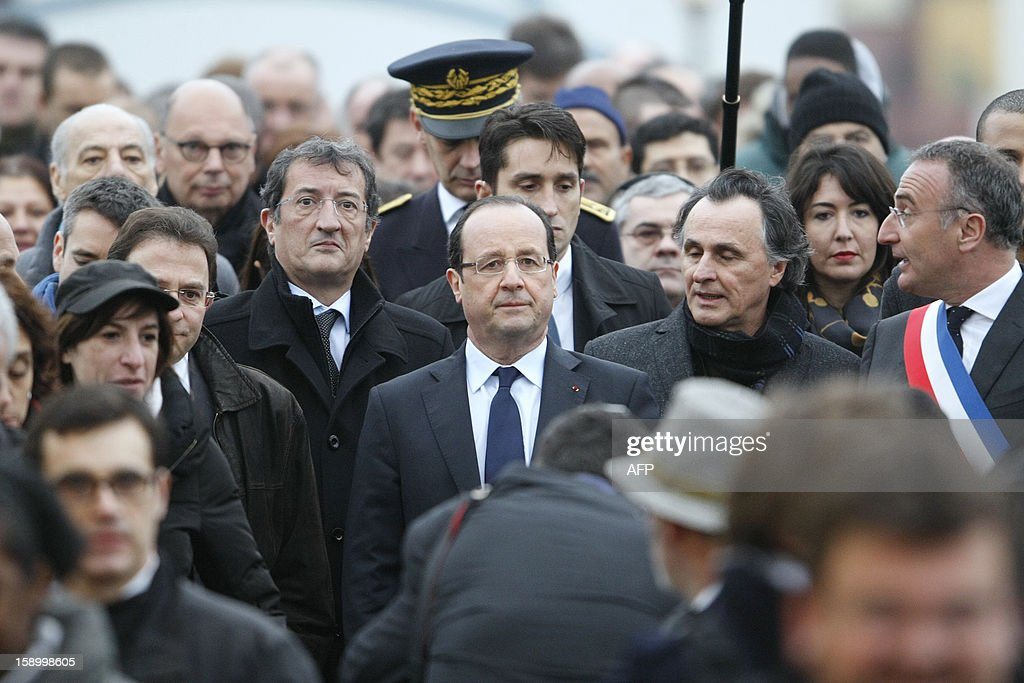 French President Francois Hollande (C) flanked by French Junior Minister for Cities, Francois Lamy (C,L) visits a district in renovation in Val-de-Reuil, northwestern France, on January 5, 2013, during a tour in Normandy.