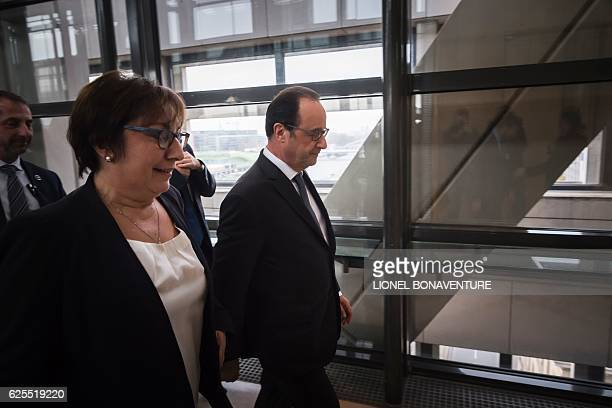 French president Francois Hollande flanked by French junior minister for Trade Handicraft and Social and Solidarity Economy Martine Pinville leaves...