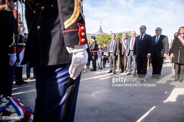 French President Francois Hollande flanked by French Junior Minister for Veterans JeanMarc Todeschini and mayor of Paris Anne Hdalgo attends a...