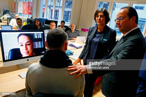 French President Francois Hollande flanked by French Labor Minister Myriam El Khomri speaks with a man sitting in front of a computer screen as an...