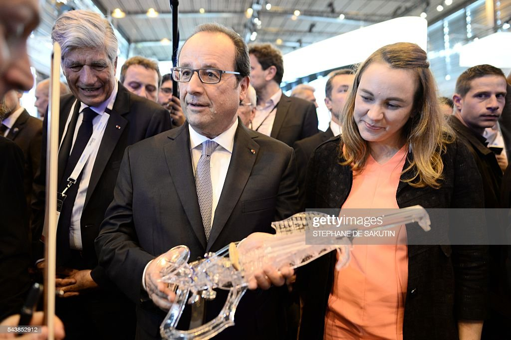 French President Francois Hollande (C) flanked by French Minister of State for the Digital Sector Axelle Lemaire (R) and Publicis Group Directory Board Chairman Maurice Levy (L), holds a 3Dvarius, 3D printed electric violin, during a visit to the Viva technology event in Paris on June 30, 2016. SAKUTIN