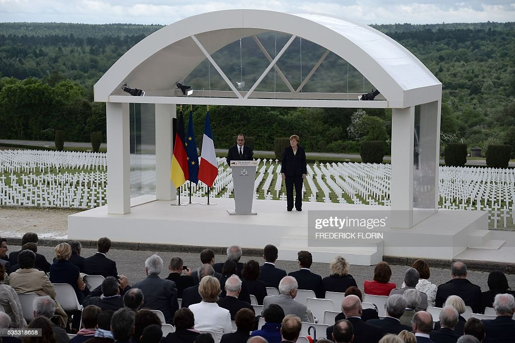 French President Francois Hollande (L), flanked by German Chancellor Angela Merkel delivers a speech at the Douaumont Ossuary (Ossuaire de Douaumont), northeastern France, on May 29, 2016, during a remembrance ceremony to mark the centenary of the battle of Verdun. The battle of Verdun, in 1916, was one of the bloodiest episodes of World War I. The offensive which lasted 300 days claimed more than 300,000 lives. / AFP / POOL / FREDERICK