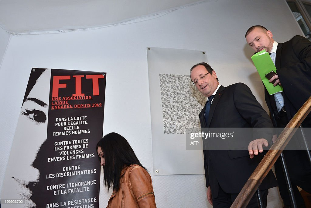 French President Francois Hollande (2ndR) flanked by his press and communication adviser Christian Gravel (R), visits on November 25, 2012 in Paris, a center housing women victims of domestic violence, during the International Day for the Elimination of Violence Against Women. Since 1999, the United Nations each year invites governments, international organizations and NGOs to organize activities designed to encourage the public to fight such violence. At left, a poster of the FIT association, 'Une femme, un toit' (A woman, a roof). LANGLOIS
