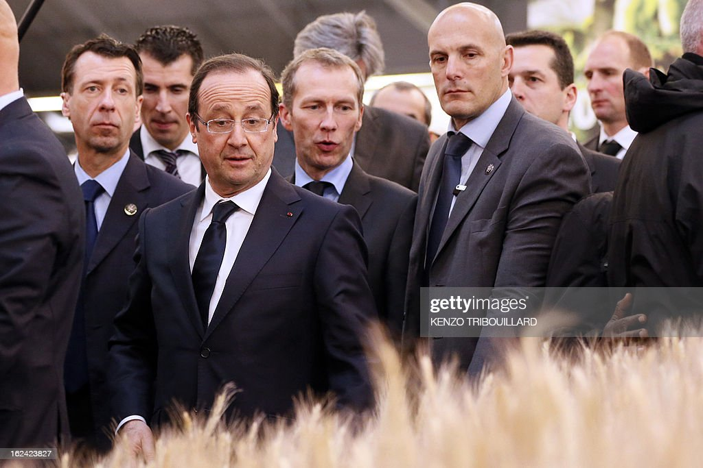 French President Francois Hollande (2ndL), flanked by Junior Minister for Food Industry Guillaume Garot (C) passes by wheat plants as he visits the 50th International Agriculture Fair of Paris at the Porte de Versailles exhibition center, on February 23, 2013 in Paris.