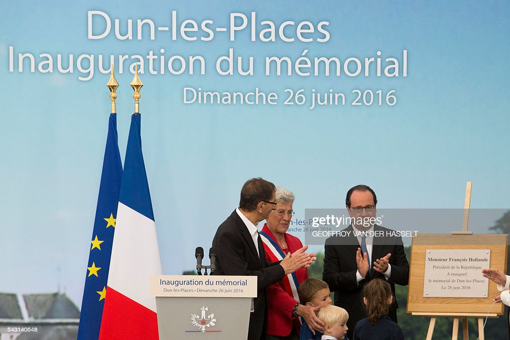 French President Francois Hollande (R), flanked by Lucienne Biardoux (C), Mayor of Dun-les-Places unveils the inaugural plaque of the Dun-les-Places memorial during the inauguration ceremony in tribute of the victims killed during the Second World War in Dun-les-Places on June 26, 2016. / AFP / GEOFFROY
