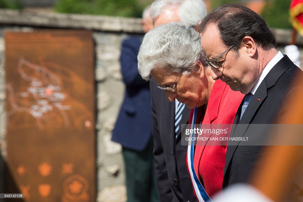 French President Francois Hollande (C), flanked by Lucienne Biardoux, Mayor of Dun-les-Places (L), reacts during the inauguration ceremony of the memorial of Dun-les-Places in tribute of the victims killed during the Second World War in Dun-les-Places on June 26, 2016. / AFP / GEOFFROY