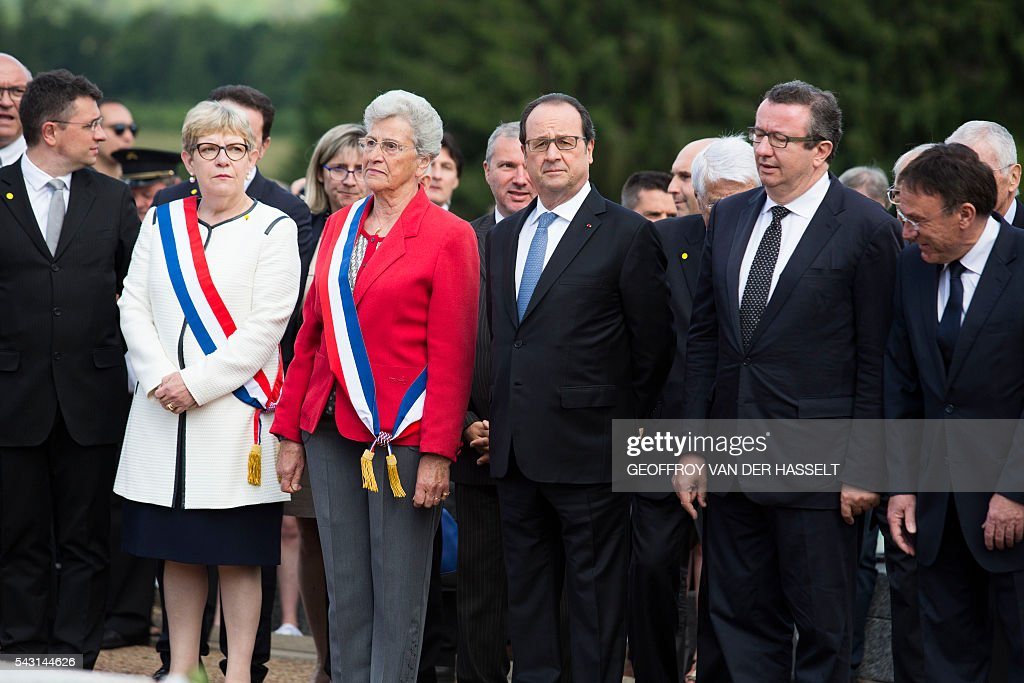 French President Francois Hollande (C), flanked by Lucienne Biardoux, Mayor of Dun-les-Places (L) and Christan Paul (R) member of parliament of the socialit party, stands guard during the inauguration ceremony of the memorial of Dun-les-Places in tribute of the victims killed during the Second World War in Dun-les-Places on June 26, 2016. / AFP / GEOFFROY