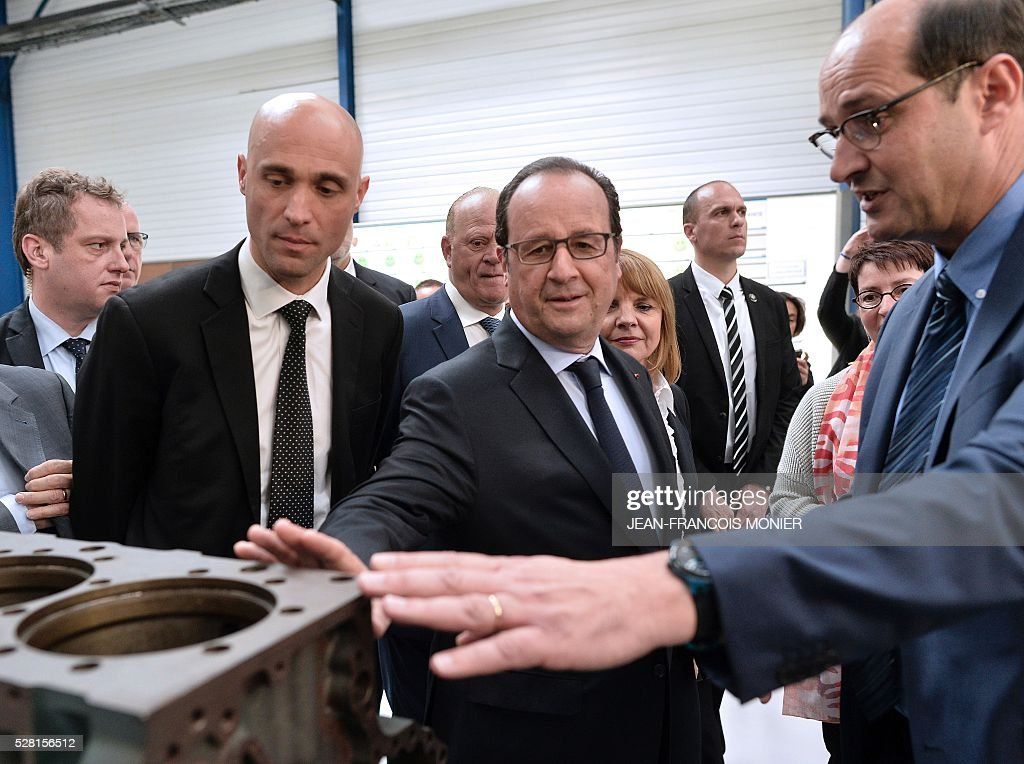 French President Francois Hollande (C) flanked by Mecachrome's French Chief Executive Officer Arnaud de Ponnat (L), listens to MK Automotive Mecachrome Director Etienne Braud during a visit at the MK Automotive Mecachrome plant, on May 4, 2016 in Sable-sur-Sarthe, northwestern France. / AFP / JEAN