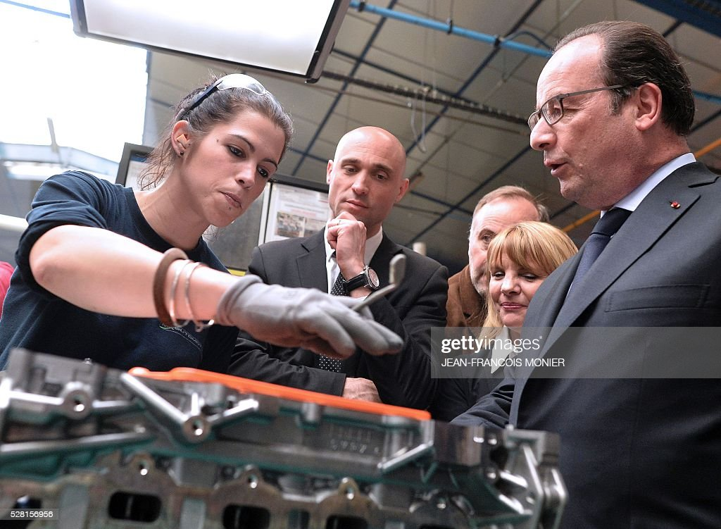 French President Francois Hollande (R) flanked by Mecachrome's French Chief Executive Officer Arnaud de Ponnat (C) looks a Renault engine cylinder head during a visit at the MK Automotive Mecachrome plant on May 4, 2016 in Sable-sur-Sarthe, northwestern France. / AFP / JEAN