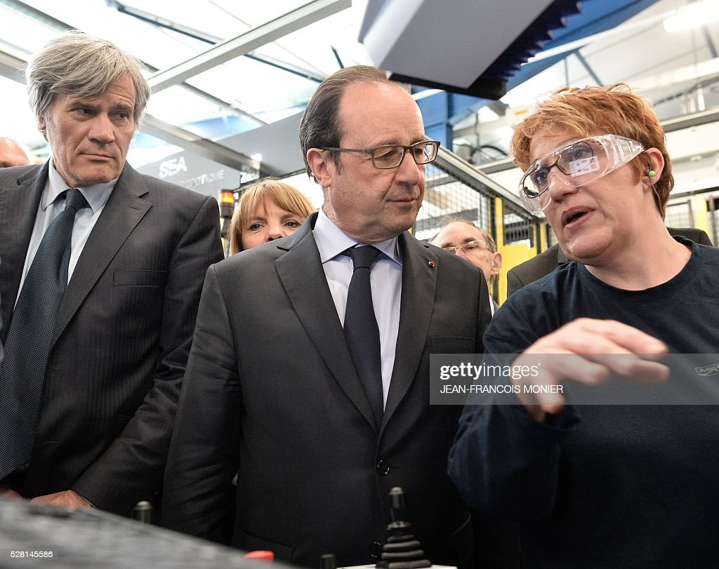 French President Francois Hollande (C), flanked with French Agriculture minister and Government spokesperson Stephane Le Foll (L), speaks with a worker as he visits the MK Automotive Mecachrome plant on May 4, 2016 in Sable-sur-Sarthe, northwestern France. / AFP / JEAN