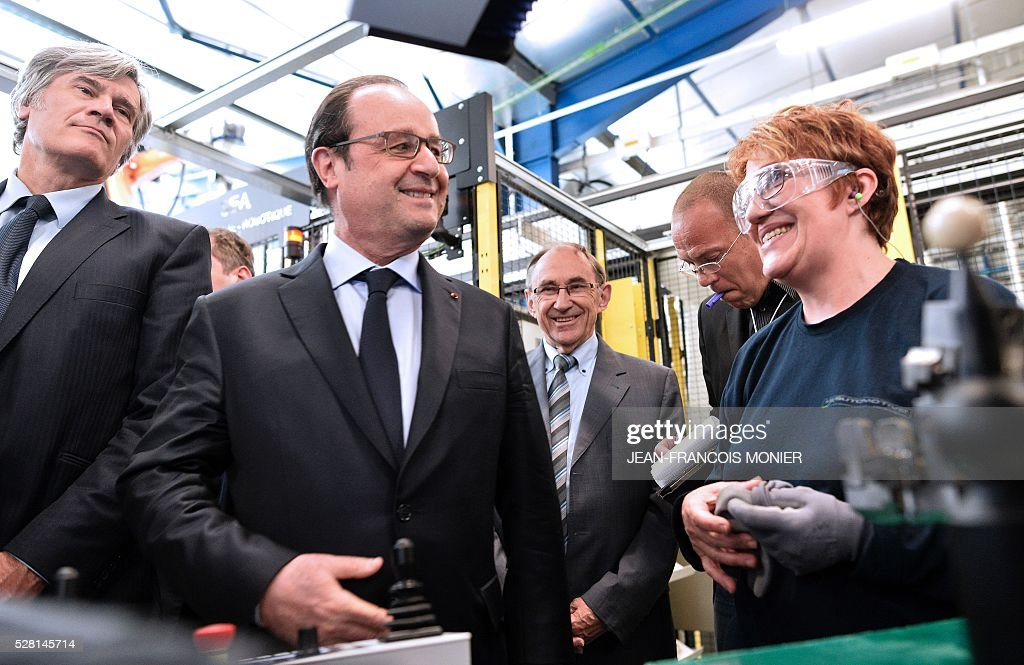 French President Francois Hollande (2R), flanked with French Agriculture minister and Government spokesperson Stephane Le Foll (3R), speaks with a worker as he visits the MK Automotive Mecachrome plant on May 4, 2016 in Sable-sur-Sarthe, northwestern France. / AFP / JEAN