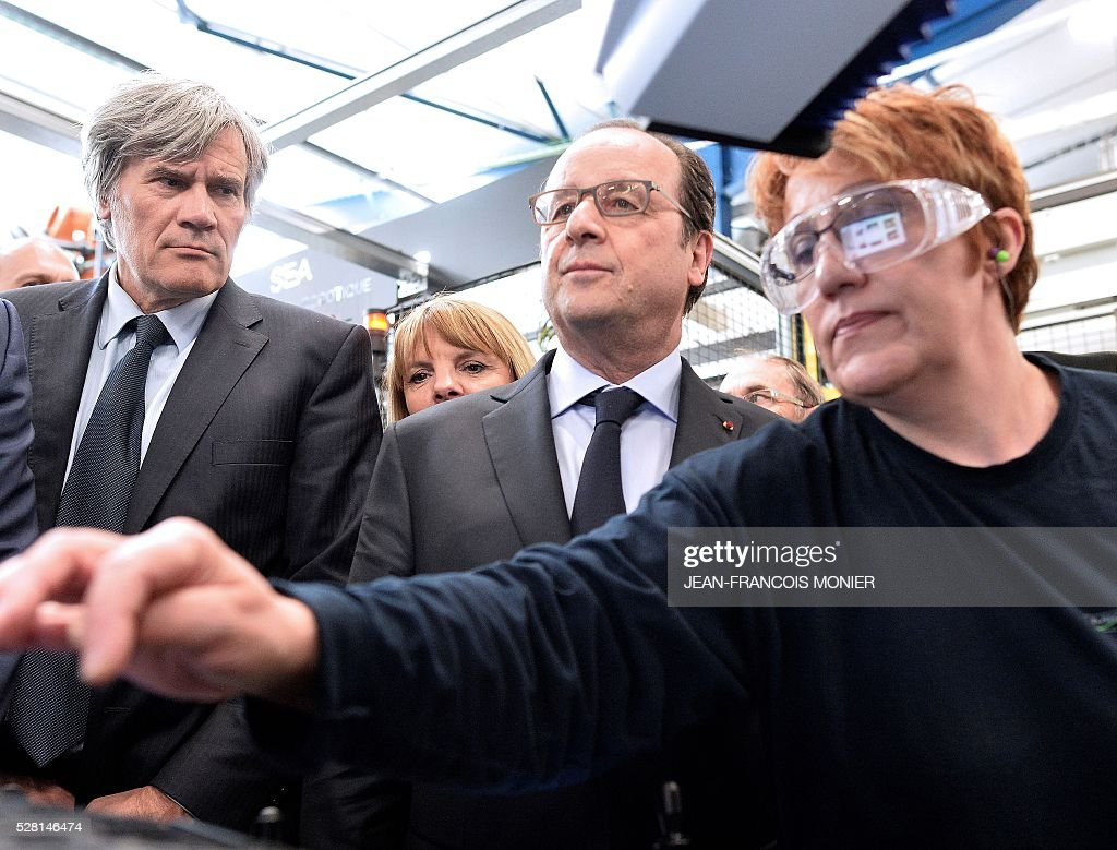 French President Francois Hollande (C), flanked with French Agriculture minister and Government spokesperson Stephane Le Foll (L) looks on as he visits the MK Automotive Mecachrome plant on May 4, 2016 in Sable-sur-Sarthe, northwestern France. / AFP / JEAN