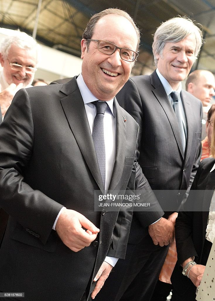 French President Francois Hollande (L), flanked with French Agriculture minister and Government spokesperson Stephane Le Foll, smiles during a visit at the MK Automotive Mecachrome plant on May 4, 2016 in Sable-sur-Sarthe, northwestern France. / AFP / JEAN