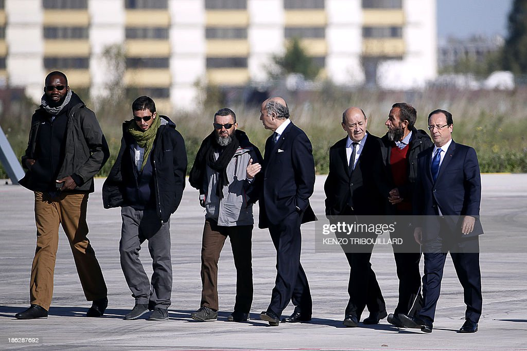 French President Francois Hollande (R), French Defence Minister Jean-Yves Le Drian (3rdR) and French Foreign Affairs minister Laurent Fabius (4thR) welcome (FromL) former French hostages Thierry Dol, Pierre Legrand, Marc Feret and Daniel Larribe (2ndL) upon their arrival at the military airport of Villacoublay outside Paris, on October 30, 2013. Four French hostages who were kidnapped by Al-Qaeda in the Islamic Maghreb in northern Niger in 2010 have been released on October 29. Frenchmen Thierry Dol, Daniel Larribe, Pierre Legrand and Marc Feret were working for French nuclear giant Areva when they were kidnapped on September 16, 2010, from a uranium compound in Arlit, north-central Niger. AFP PHOTO / KENZO TRIBOUILLARD