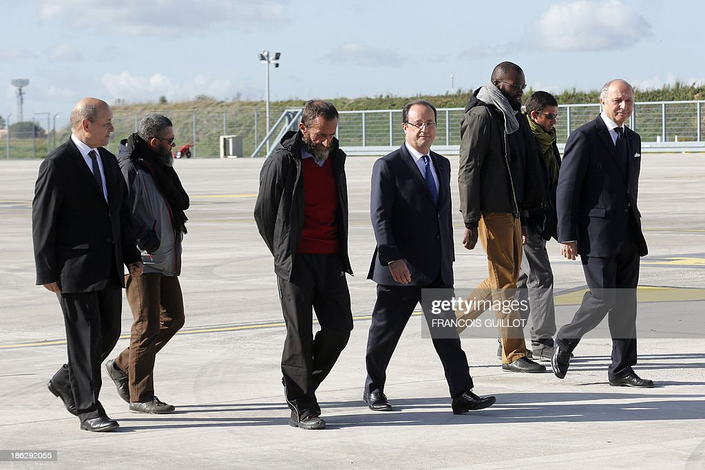 French President Francois Hollande (C), French Defence Minister Jean-Yves Le Drian (L) and French Foreign Affairs minister Laurent Fabius (R) welcome (FromL) former French hostages Marc Feret, Daniel Larribe, Thierry Dol and Pierre Legrand, upon their arrival at the military airport of Villacoublay outside Paris, on October 30, 2013. Four French hostages who were kidnapped by Al-Qaeda in the Islamic Maghreb in northern Niger in 2010 have been released on October 29. Frenchmen Thierry Dol, Daniel Larribe, Pierre Legrand and Marc Feret were working for French nuclear giant Areva when they were kidnapped on September 16, 2010, from a uranium compound in Arlit, north-central Niger.